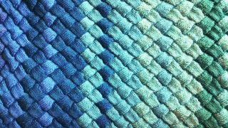 an entrelac blanket in various shades of blue and green