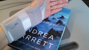 hand in a wrist brace atop a book